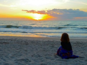 little girl watching sunset
