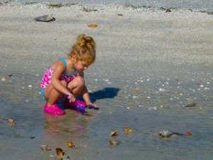 little girl digging beach sand
