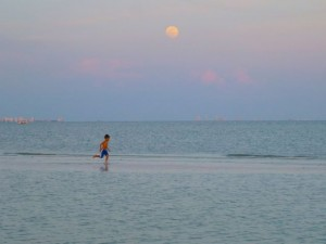 boy running full moon sanibel