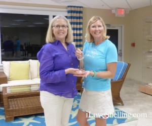 pam rambo presents suzanne with winning necklace