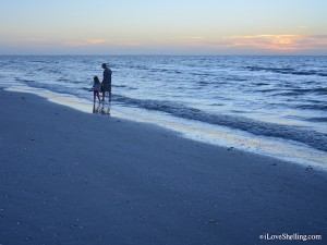 father and daughter on the beach at sunrise